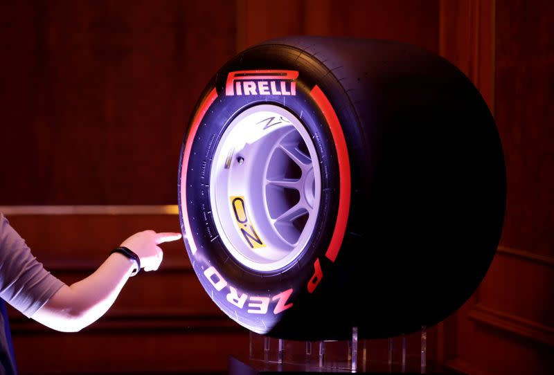 FILE PHOTO: A woman touches a Pirelli tyre displayed for a news conference by ChemChina and Pirelli in Beijing