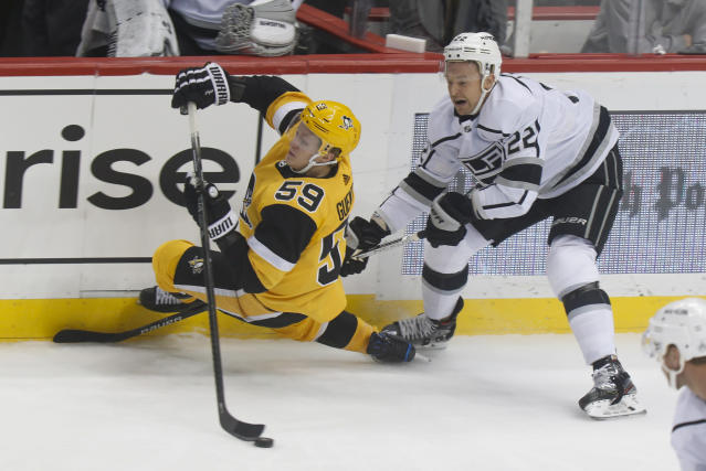 Pittsburgh Penguins' Jake Guentzel (59) reaches for the puck as Los Angeles Kings' Trevor Lewis (22) defends along the boards during the first period of an NHL hockey game, Saturday, Dec. 14, 2019, in Pittsburgh. (AP Photo/Keith Srakocic)