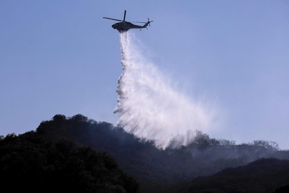 A helicopter makes a water drop to put out hotspots in Topanga, west of Los Angeles, on July 19.