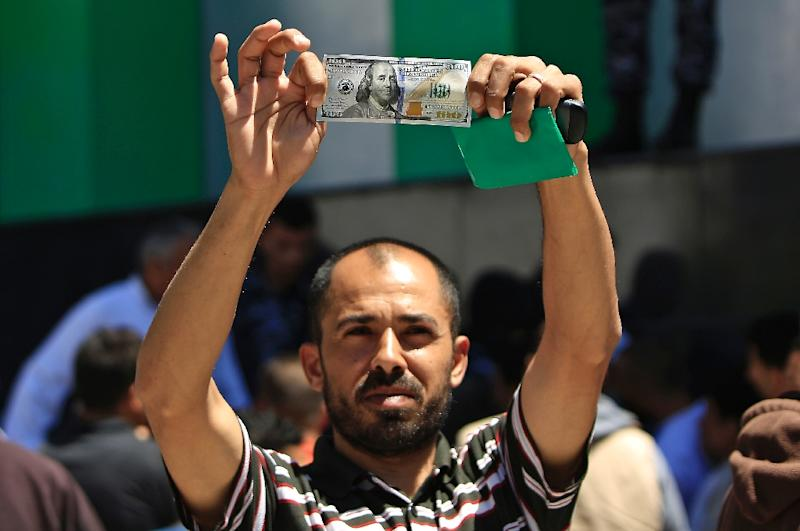 A Palestinian man displays a 100 dollar bill, part of a multi-million aid package allocated by Qatar, in Gaza City on May 13, 2019