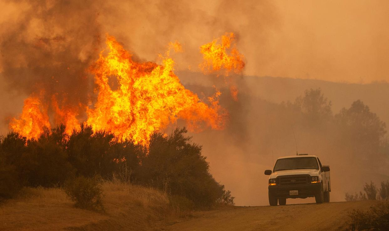 A truck passes by flames during the Ranch Fire.