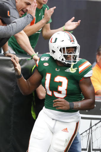 Miami running back DeeJay Dallas (13) celebrates a touchdown during the first half of an NCAA college football game against Louisville, Saturday, Nov. 9, 2019, in Miami Gardens, Fla. (AP Photo/Wilfredo Lee)