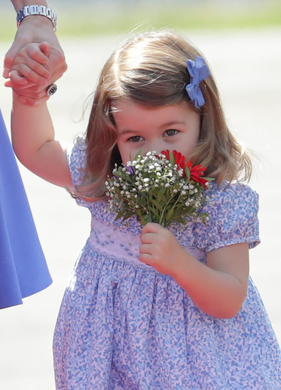 Charlotte, the daughter of Britain's Prince William and his wife Catherine, Duchess of Cambridge, smells a bunch of flowers after arriving at Tegel Airport in Berlin, Germany, 19 July 2017. Photo: Kay Nietfeld/dpa (Photo by Kay Nietfeld/picture alliance via Getty Images)