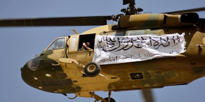 A helicopter displaying a Taliban flag flies above Taliban supporters gathered to celebrate the US withdrawal of all its troops out of Afghanistan, in Kandahar on September 1, 2021 following the Talibans military takeover of the country.