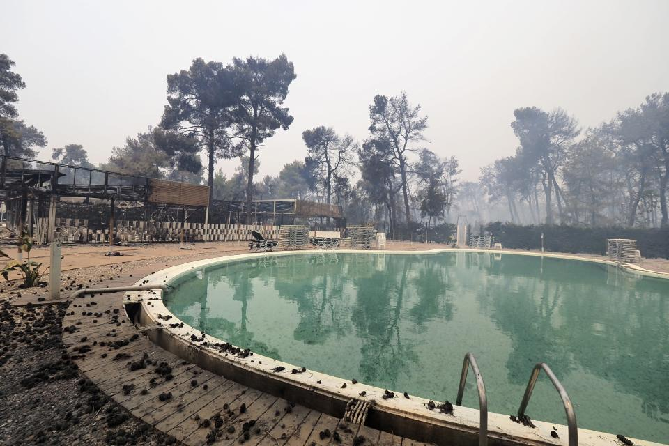 A burnt camping during a wildfire in Agia Anna village on the island of Evia, about 146 kilometers (91 miles) north of Athens, Greece, Friday, Aug. 6, 2021. Thousands of people fled wildfires burning out of control in Greece and Turkey on Friday, including a major blaze just north of the Greek capital of Athens that claimed one life, as a protracted heat wave left forests tinder-dry and flames threatened populated areas and electricity installations. (AP Photo/Thodoris Nikolaou)