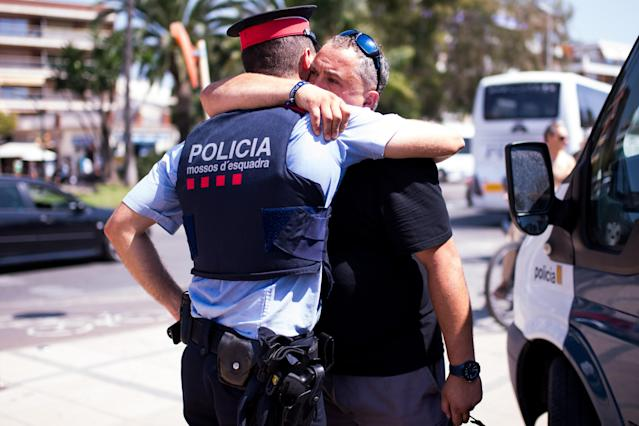<p>A man embraces a police officer on the spot where five terrorists were shot by police on August 18, 2017 in Cambrils, Spain. (Photo: Alex Caparros/Getty Images) </p>
