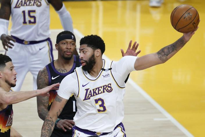Lakers forward Anthony Davis is guarded by Phoenix Suns guard Devin Booker and forward Torrey Craig in the first quarter.