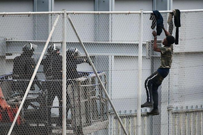 A man attempts to scale a fence as border guards stand on the other side.