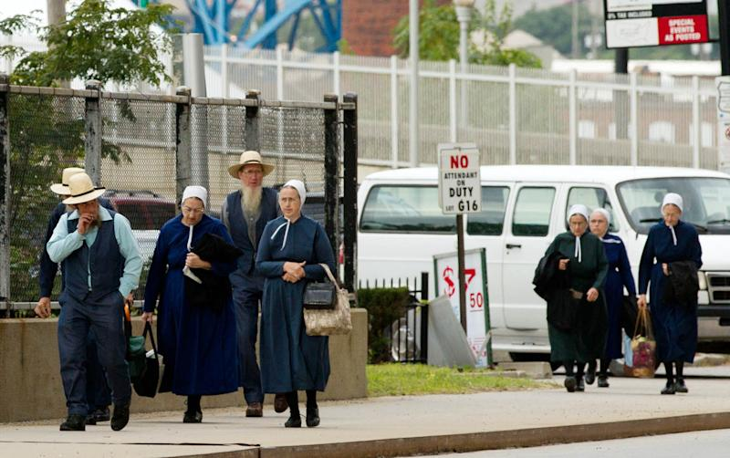 Members of the Amish community walk to the U.S. Federal Courthouse in Cleveland on Wednesday, Sept. 19, 2012. Jurors are beginning a third day of deliberations in the trial of 16 people accused of hate crimes in hair- and beard-cutting attacks against fellow Amish in Ohio. (AP Photo/Scott R. Galvin)