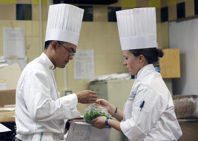 West Point Cadet Chuck Ya of Austin, Texas, left, and Culinary Institute of America student Leah Pfeiffer, of Fairfax, Va., handle ingredients for a recipe during an exchange program at the culinary school on Wednesday, Oct. 16, 2013, in Hyde Park, N.Y. (AP Photo/Mike Groll)