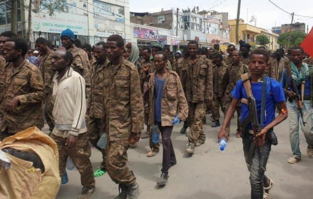 Tigrayan fighters escort captured Ethiopian soldiers to a detention camp after retaking the Tigrayan capital of Mekelle on July 2. (Reuters - image credit)