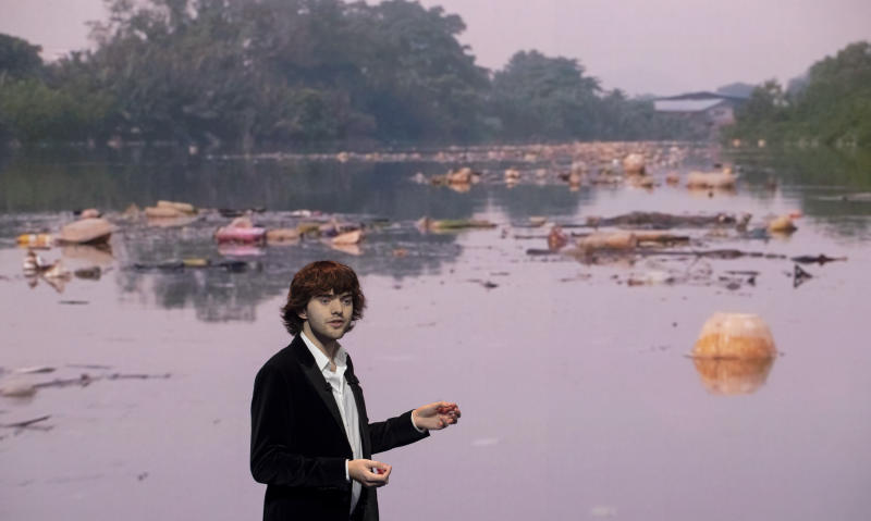Young Dutch inventor Boyan Slat presents his plans for the Interceptor, a plastic-gathering floating device, in front of a video of a polluted river, during a presentation in Rotterdam, Netherlands, Saturday, Oct. 26, 2019. Slat is taking his effort to clean up floating plastic from the Pacific Ocean to rivers to catch garbage before it reaches the seas. (AP Photo/Peter Dejong)