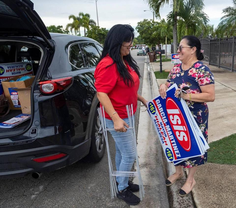 Hialeah mayoral candidate Isis Garcia-Martinez, left, leaves some signs for a supporter on Sept. 24, 2021.