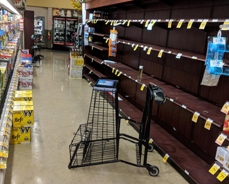 FILE - In this May 29, 2018, file photo, supermarket shelves are stripped bare of bottled water in Salem, Ore., after officials warned residents that tap water was unsafe for children and the elderly due to an algae bloom. Researchers and officials across the country say increasingly frequent toxic algae blooms are another bi-product of global warming. They point to looming questions about their effects on human health. (AP Photo/Tom James, File)