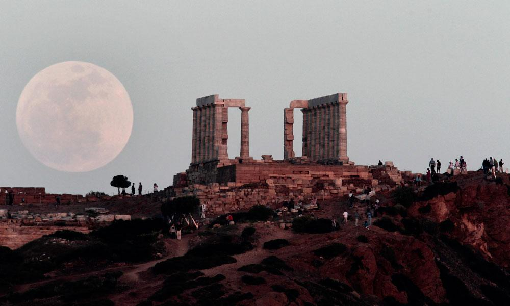 "The full moon rises behind the Temple of Poseidon in Cape Sounion, south east of Athens, Greece, while tourists watch, on Saturday, May 5, 2012.  Saturday's event is a ""supermoon,"" the closest and therefore the biggest and brightest full moon of the year."