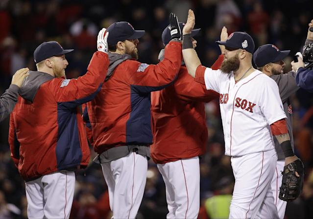 Boston Red Sox's Mike Napoli, right, celebrates with John Lackey, center, and teammates after Game 1 of baseball's World Series against the St. Louis Cardinals Wednesday, Oct. 23, 2013, in Boston. The Red Sox won 8-1 to take a 1-0 lead in the series. (AP Photo/David J. Phillip)