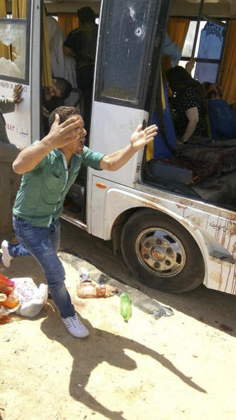 A man screams beside a bus carrying Coptic Christians which came under attack outside Cairo, Friday, Nov. 2, 2018. Islamic militants on Friday ambushed a bus carrying Christian pilgrims on their way to a remote desert monastery south of the Egyptian capital, killing at least seven and wounding a dozen more, the Interior Ministry said.(Egypt's Coptic Orthodox Church via AP)