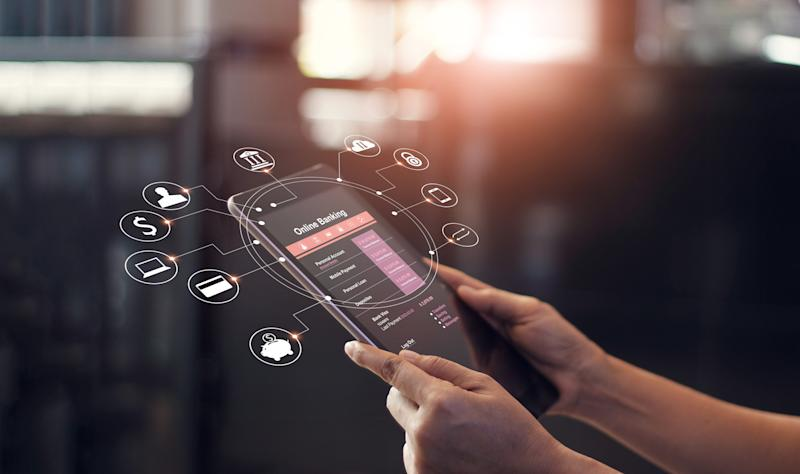 """A close-up of a smartphone with the words """"Digital Banking"""" on it, and animation icons for financial tools circle around it."""