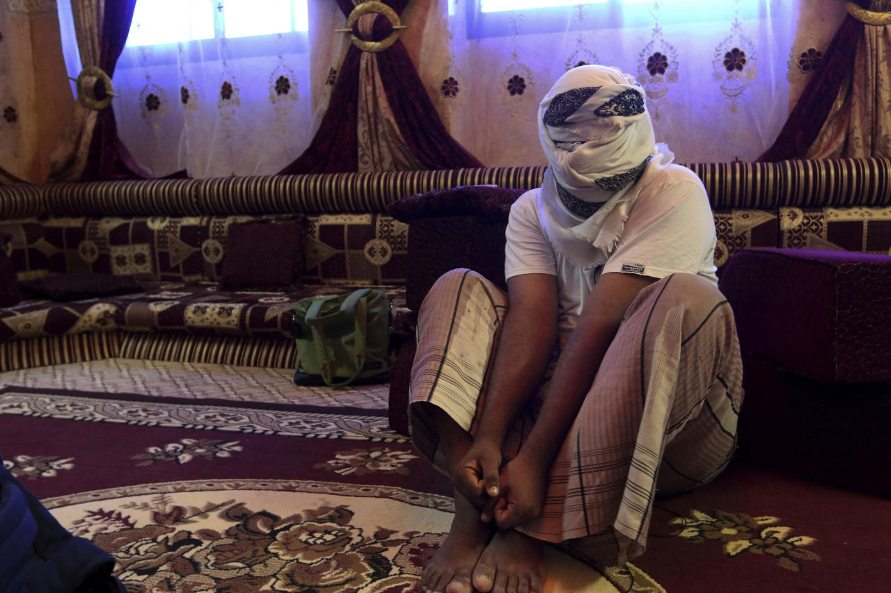 A former detainee covers his face for fear of being detained again, as he shows how he was kept in handcuffs and leg shackles while held in a secret prison at Riyan airport in the Yemeni city of Mukalla on May 11, 2017. More than two years of civil war have led to continually compounding disasters in Yemen. Fighting rages on in a deadly stalemate, the economy has been bombed into ruins, hunger is widespread, and a new misery has been added: Cholera, the world's biggest current outbreak with more than 200,000 cases. (AP Photo/Maad El Zikry, File)