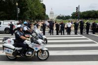 Law enforcement officers salute as a ceremonial procession in honor of a police officer wounded at the Pentagon passes the U.S. Capitol in Washington