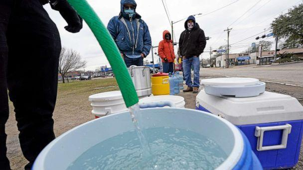PHOTO: A water bucket is filled as others wait in near freezing temperatures to use a hose from public park spigot, Feb. 18, 2021, in Houston. (David J. Phillip/AP)