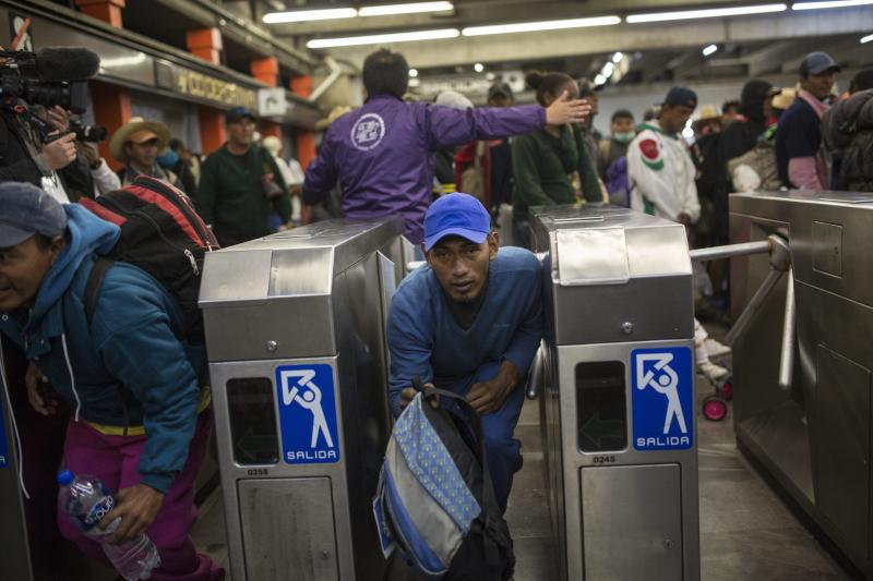 A Central American migrant bypasses a subway turnstile after leaving the temporary shelter at the Jesus Martinez stadium, in Mexico City, Friday, Nov. 9, 2018. About 500 Central American migrants headed out of Mexico City on Friday to embark on the longest and most dangerous leg of their journey to the U.S. border, while thousands more were waiting one day more at the stadium. (AP Photo/Rodrigo Abd)