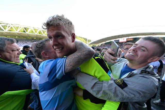 "Soccer Football - Premier League - Huddersfield Town vs Arsenal - John Smith's Stadium, Huddersfield, Britain - May 13, 2018 Huddersfield Town's Jonas Lossl celebrates with fans on the pitch at the end of the match REUTERS/Peter Powell EDITORIAL USE ONLY. No use with unauthorized audio, video, data, fixture lists, club/league logos or ""live"" services. Online in-match use limited to 75 images, no video emulation. No use in betting, games or single club/league/player publications. Please contact your account representative for further details."