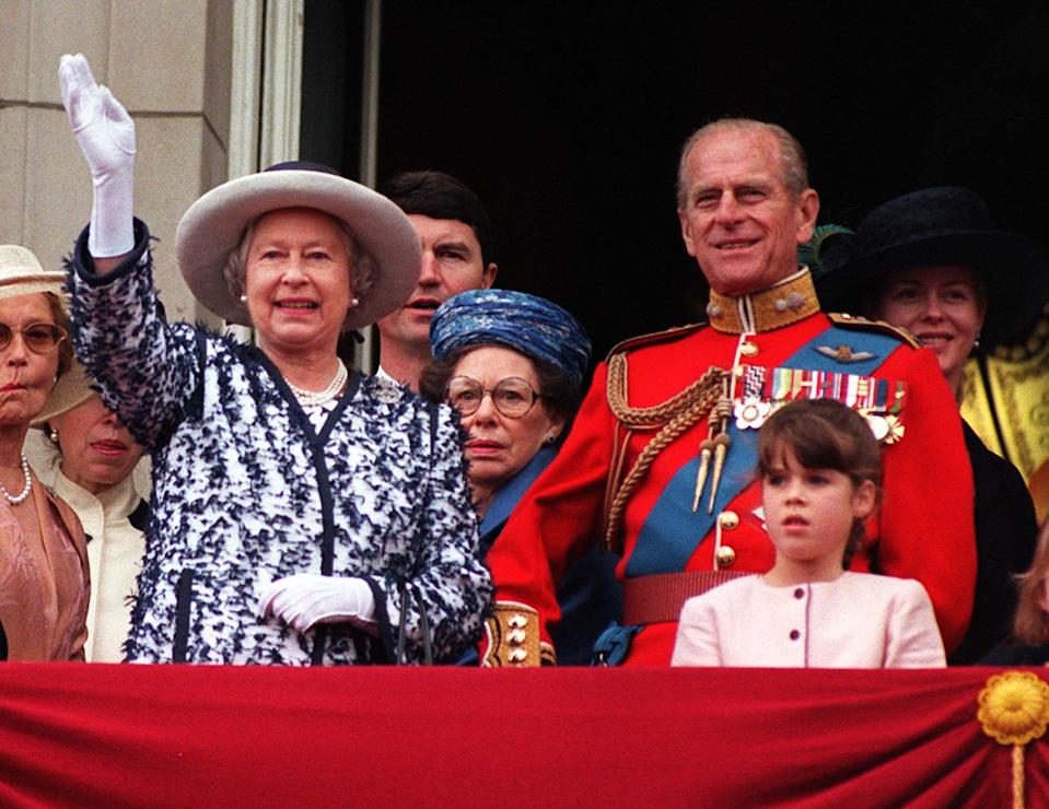 The Queen waves to the crowds as she stands on the balcony of Buckingham Palace with the Duke of Edinburgh and other members of the Royal Family after watching the traditional fly-past as part of the Trooping of the Colour in honour of the Her official birthday today (Saturday). Left to right: The Queen, Tim Laurence (Princess Anne's husband) Princess Margaret (wearing blue hat), The Duke of Edinburgh, Princess Eugenie (pink dress), Lady Helen Taylor (dressed in black), unidentified young girl and The Duke of Kent. See PA story ROYAL Trooping. WPA rota picture by John Stillwell/PA   (Photo by John Stillwell - PA Images/PA Images via Getty Images)