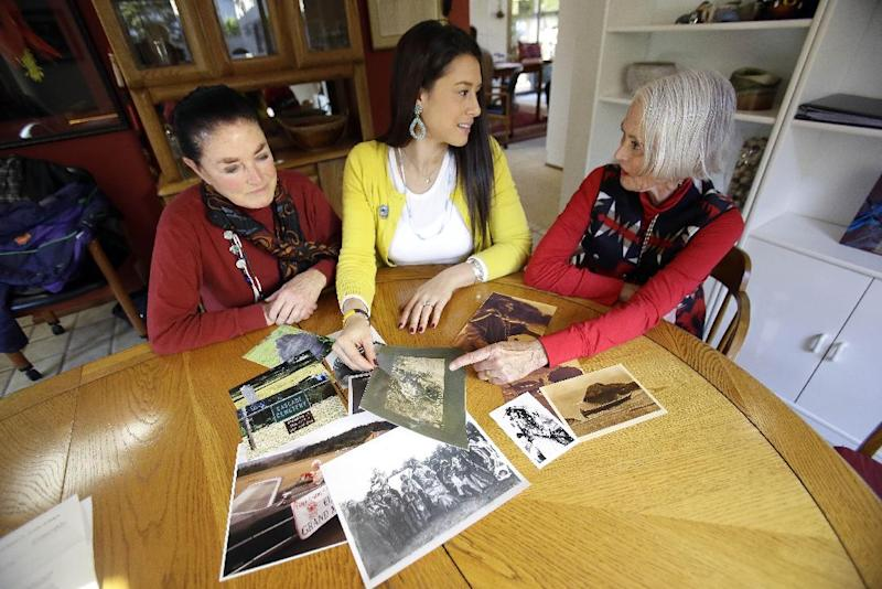Mia Prickett, middle, shares a collection of family photos with great aunt's Marilyn Portwood, right, and Val Alexander in Portland, Ore., Thursday, Jan. 16, 2014. Prickett's ancestor Tumulth, a leader of the Cascade Indians along the Columbia River, was one of the chiefs who signed an 1855 treaty that helped establish the Confederated Tribes of the Grand Ronde in Oregon. But the Grand Ronde now wants to disenroll Prickett and 79 relatives because they no longer satisfy new enrollment requirements. (AP Photo/Don Ryan)