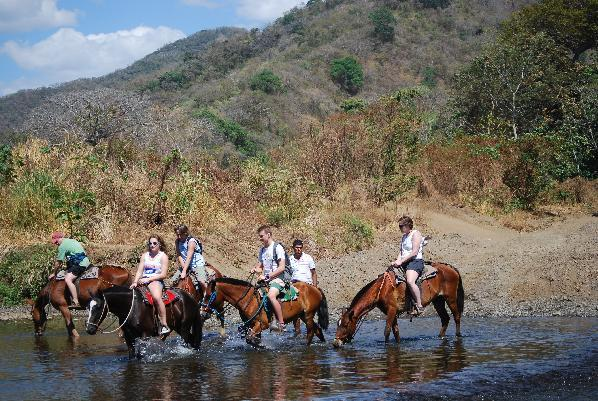 This February 2014 photo released by Kristina MacKulin shows a group of horseback riders on a tour with outfitters Nosara Paradise Rentals, in Nosara, Costa Rica. Nosara is a scenic coastal region with a variety of outdoor recreation activities for visitors. (AP Photo/Kristina MacKulin)
