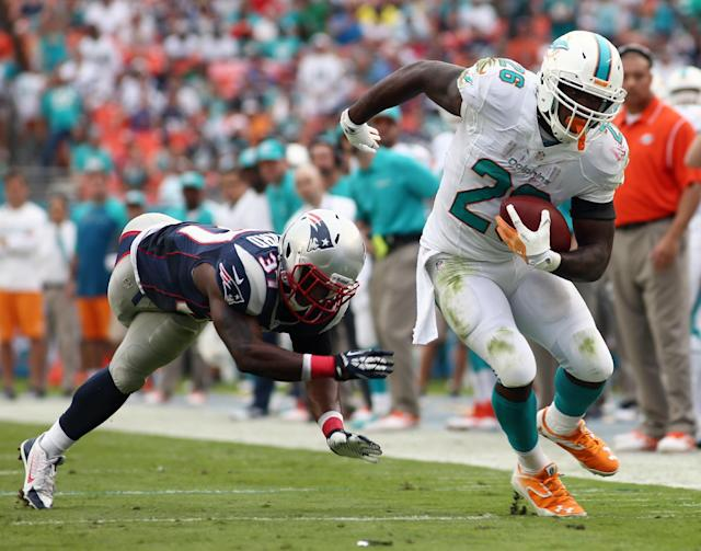 Miami Dolphins running back Lamar Miller (26) gets away from a tackle by New England Patriots cornerback Alfonzo Dennard, left, during the second half of an NFL football game, Sunday, Dec. 15, 2013, in Miami Gardens, Fla. (AP Photo/J Pat Carter)