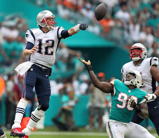 <p>Patriots quarterback Tom Brady lunges for the ball as the Dolphins Charles Harris reaches for it as well. Brady's pass attempt was deflected, and the ball came back in his direction, but it fell to the ground for an incompletion. The New England Patriots visited the Miami Dolphins in a regular season NFL football game at Hard Rock Stadium. (Jim Davis/Globe Staff) </p>