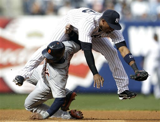 Detroit Tigers' Austin Jackson, bottom, collides with New York Yankees shortstop Eduardo Nunez while stealing second base during the first inning of a baseball game on Saturday, April 28, 2012, in New York. (AP Photo/Julio Cortez)