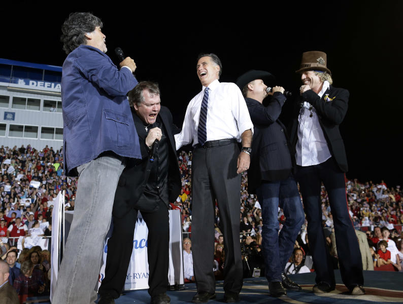 "Republican presidential candidate and former Massachusetts Gov. Mitt Romney, center, sings ""God Bless America"" during a campaign stop at the football stadium at Defiance High School in Defiance, Ohio, Thursday, Oct. 25, 2012, with, from left, Randy Owen, Meat Loaf, John Rich and Big Kenny. (AP Photo/Charles Dharapak)"
