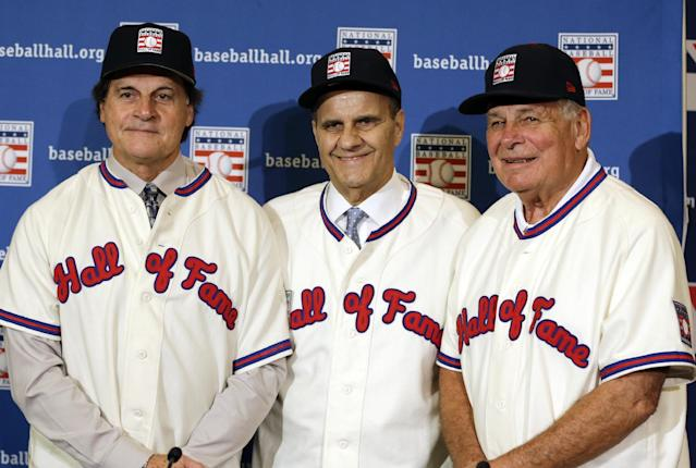 FILE - In this Dec. 9, 2013, file photo, retired managers, from left, Tony La Russa, Joe Torre and Bobby Cox gather for a photo after it was announced that they were unanimously elected to the baseball Hall of Fame during MLB winter meetings in Lake Buena Vista, Fla. La Russa will not have any logo on his cap in his Hall of Fame plaque, the Hall said Thursday, Jan. 23, 2014. Torre's will have a Yankees logo, while Cox's whill have a Braves logo. (AP Photo/John Raoux, File)