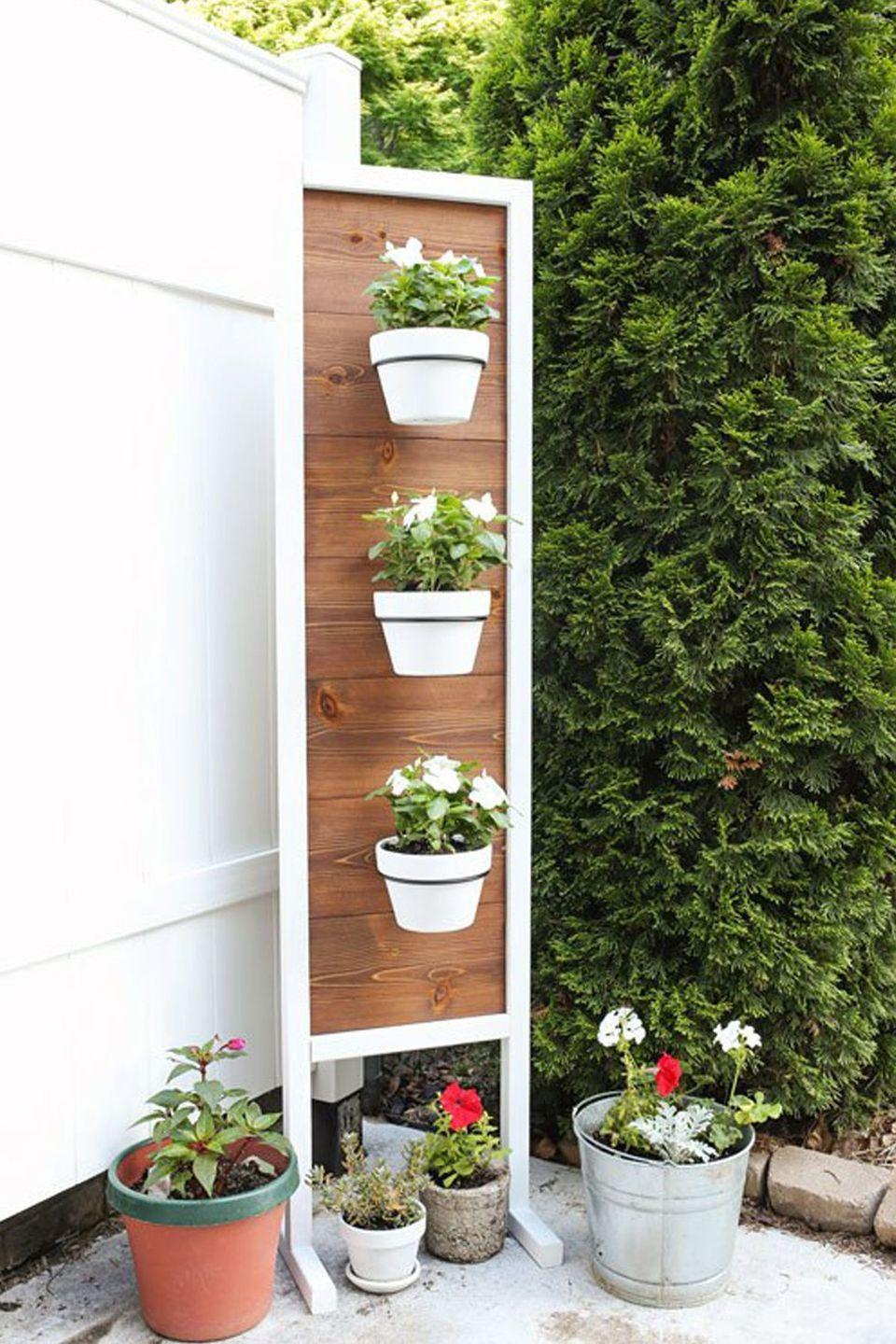 """<p>For a garden that doubles as decor, affix ceramic pots to a framed piece of cedar or pine wood. For extra impact, keep flowers in the same color theme, and sprinkle a few extras throughout the rest of your outdoor space. </p><p><em><a href=""""https://angelamariemade.com/2017/06/diy-vertical-planter-stand/"""" rel=""""nofollow noopener"""" target=""""_blank"""" data-ylk=""""slk:Get the tutorial at Angela Marie Made »"""" class=""""link rapid-noclick-resp"""">Get the tutorial at Angela Marie Made »</a></em></p>"""