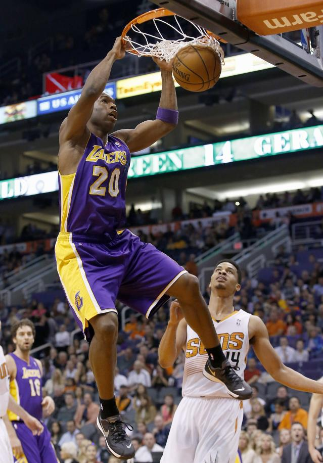 Los Angeles Lakers' Jodie Meeks (20) dunks as he gets past Phoenix Suns' Gerald Green, right, during the first half of an NBA basketball game Wednesday, Jan. 15, 2014, in Phoenix. (AP Photo/Ross D. Franklin)