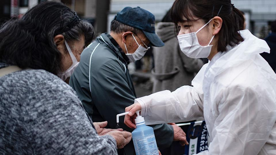 Pictured here, locals in Japan wear masks and use hand sanitiser amid the global Covid-19 pandemic.