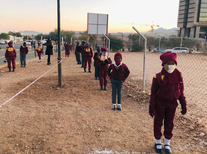 Primary school students keep space between them as they wait before entering school in Windhoek, Namibia on July 7. Primary schools in Namibia reopened under strict health guidelines after COVID-19 shutdowns with students wearing masks and conducting social distancing.