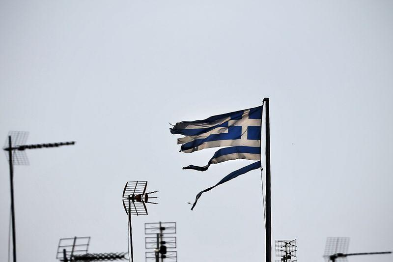A frayed Greek national flag flutters among antennas atop a building in central Athens