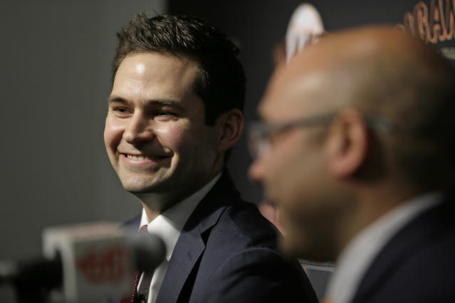 San Francisco Giants general manager Scott Harris, left, smiles as he is introduced by president of baseball operations Farhan Zaidi during a news conference at Oracle Park Monday, Nov. 11, 2019, in San Francisco. The Giants hired Harris from the Chicago Cubs to become general manager, filling a void of more than a year after the club had gone without a GM during Zaidi's first season in the position.(AP Photo/Eric Risberg)