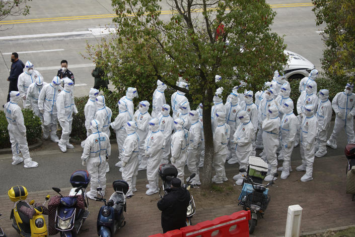 Security workers in protective suit prepare for administering COVID-19 testings for workers at the parking lot of the Shanghai Pudong International Airport in Shanghai, Monday, Nov. 23, 2020. Chinese authorities are testing millions of people, imposing lockdowns and shutting down schools after multiple locally transmitted coronavirus cases were discovered in three cities across the country last week. (AP Photo)