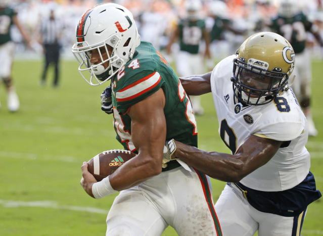 "Miami running back <a class=""link rapid-noclick-resp"" href=""/ncaaf/players/267318/"" data-ylk=""slk:Travis Homer"">Travis Homer</a> (24) is slowed down by Georgia Tech defensive back Step Durham (8) as he heads in for a touch down during the first half of an NCAA College football game, Saturday, Oct. 14, 2017 in Miami Gardens, Fla. (AP Photo/Wilfredo Lee)"