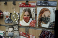 A Christmas themed face mask to try to curb the spread of coronavirus is displayed in the front window of a store selling items aimed at tourists in central London, Wednesday, Oct. 21, 2020. The South Yorkshire region of northern England is being placed under the country's tightest restrictions to curb the coronavirus — joining a densely populated swathe of the country where the measures have been imposed despite protests from local politicians. (AP Photo/Matt Dunham)