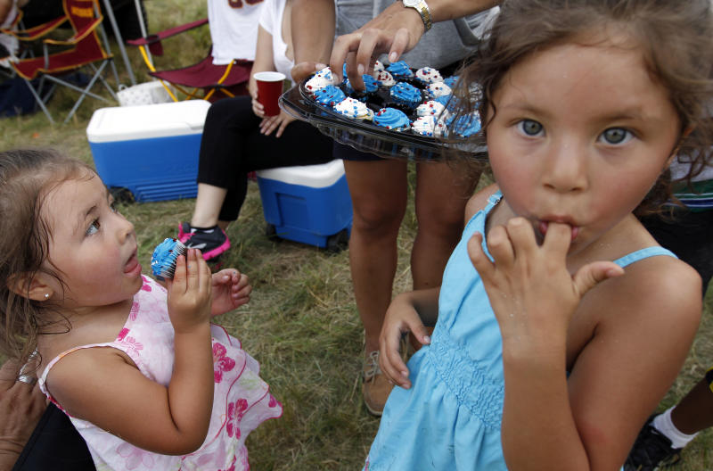 Emmarie Bonnia, 3, left, and Arhiana Bonilla, 4, enjoy cupcakes as they wait with their families to view the Independence Day fireworks celebration over the National Mall in Washington from their vantage point across the river in in Arlington, Va., Wednesday, July 4, 2012. (AP Photo/Alex Brandon)