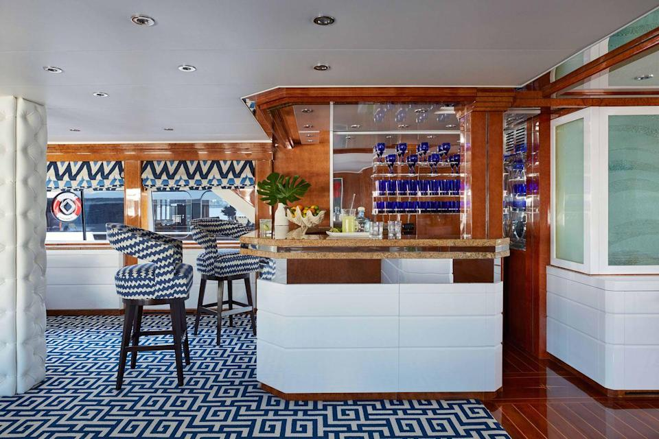 """<p>Designer <a href=""""https://www.jefflincolninteriorsnewyork.com/"""" rel=""""nofollow noopener"""" target=""""_blank"""" data-ylk=""""slk:Jeff Lincoln"""" class=""""link rapid-noclick-resp"""">Jeff Lincoln</a> updated the wet bar of <a href=""""https://www.veranda.com/luxury-lifestyle/a27651906/octopussy-yacht/"""" rel=""""nofollow noopener"""" target=""""_blank"""" data-ylk=""""slk:this retro-chic ship"""" class=""""link rapid-noclick-resp"""">this retro-chic ship</a> by coating the woodwork with white and natural lacquer. A mirrored backsplash and blue geometric patterns complete the groovy vibe. The barstools are from <a href=""""http://johnbooneinc.com/Home.aspx"""" rel=""""nofollow noopener"""" target=""""_blank"""" data-ylk=""""slk:John Boone"""" class=""""link rapid-noclick-resp"""">John Boone</a> and the carpet is by <a href=""""https://www.starkcarpet.com/"""" rel=""""nofollow noopener"""" target=""""_blank"""" data-ylk=""""slk:Stark"""" class=""""link rapid-noclick-resp"""">Stark</a>. The window shades are from <a href=""""http://quadrillefabrics.com/"""" rel=""""nofollow noopener"""" target=""""_blank"""" data-ylk=""""slk:Quadrille"""" class=""""link rapid-noclick-resp"""">Quadrille</a>.</p>"""