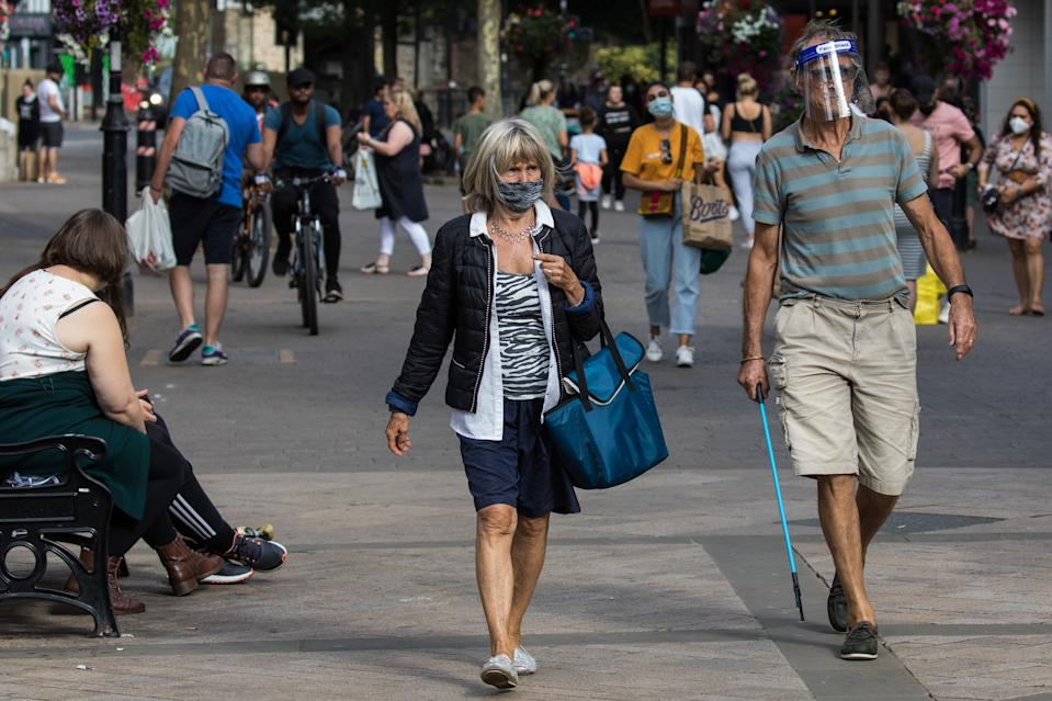 Shoppers wear face coverings and a visor to help prevent the spread of the coronavirus on 20 September 2020 in Staines-Upon-Thames, United Kingdom. The Borough of Spelthorne, of which Staines-upon-Thames forms part along with Ashford, Sunbury-upon-Thames, Stanwell, Shepperton and Laleham, has been declared an area of concern for COVID-19 by the government following a marked rise in coronavirus infections which is inconsistent with other areas of Surrey. (photo by Mark Kerrison/In Pictures via Getty Images)