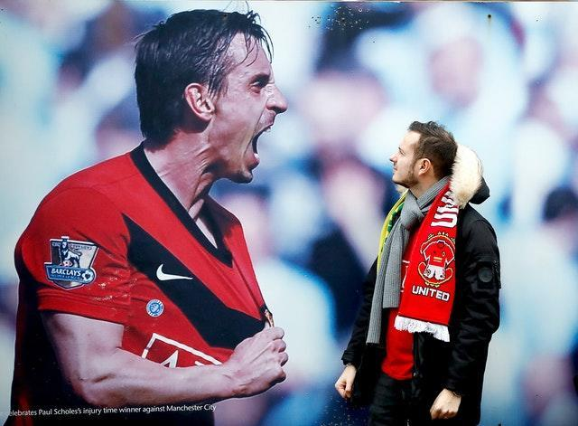A Manchester United fan admires a photograph of former player Gary Neville outside Old Trafford. Neville is pictured celebrating a derby win at Manchester City in 2010. It proved to be another victorious day for United as they thrashed Norwich 4-0 thanks to a Marcus Rashford brace and goals from Anthony Martial and Mason Greenwood
