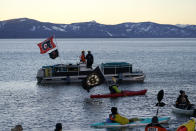 The flags of the Philadelphia Flyers, left, and the Boston Bruin, right, fly from watercraft floating on Lake Tahoe off shore of the site of the Outdoors Lake Tahoe NHL hockey game at Stateline, Nev., Sunday, Feb. 21, 2021. (AP Photo/Rich Pedroncelli)