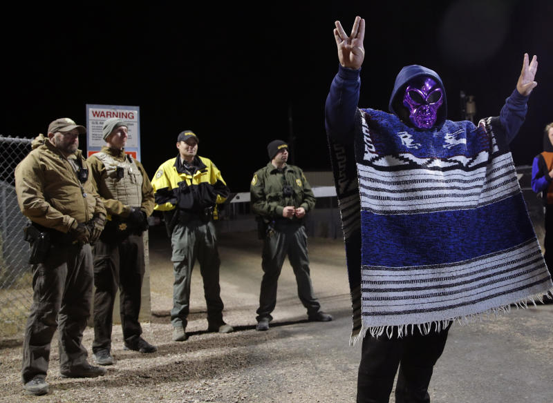 """A man in an alien mask stands at an entrance to the Nevada Test and Training Range near Area 51 Friday, Sept. 20, 2019, outside of Rachel, Nev. People gathered at the gate inspired by the """"Storm Area 51"""" internet hoax. (AP Photo/John Locher)"""